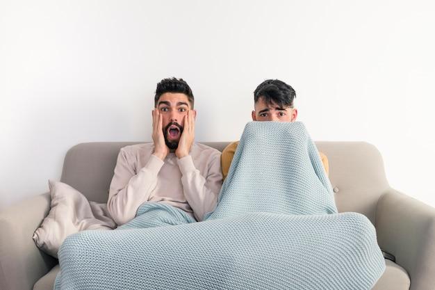 Ritratto di giovani coppie gay che si siedono sul sofà che guarda film horror sulla televisione contro la parete bianca Foto Gratuite