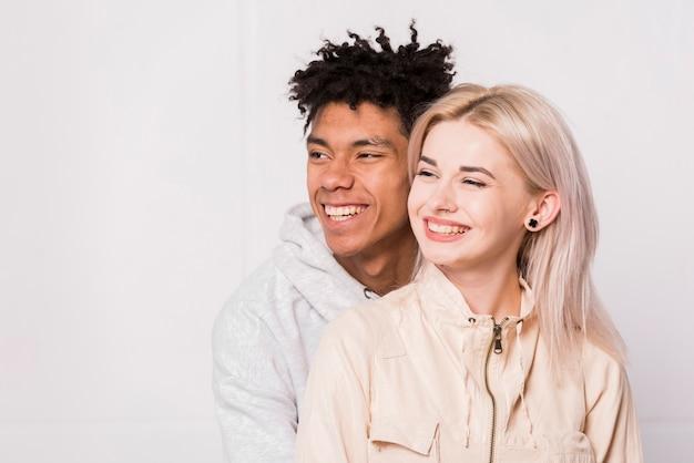 Ritratto di giovani coppie interrazziali sorridenti isolate contro priorità bassa bianca Foto Gratuite