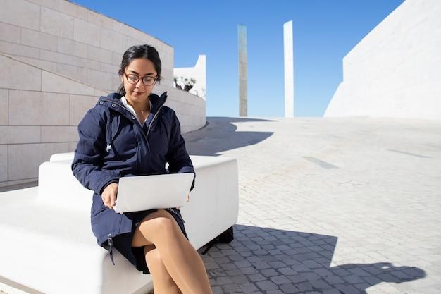 Ritratto di giovani liberi professionisti seri che lavorano al computer portatile all'aperto Foto Gratuite