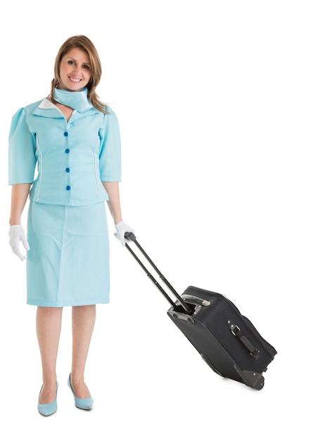 Ritratto di hostess in uniforme blu con la sua borsa Foto Premium