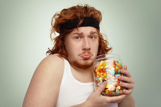 Ritratto di infelice sovrappeso obeso giovane uomo europeo dai capelli rossi che indossa fascia per capelli e canotta bianca dopo esercizi fisici, sentirsi frustrato mentre non riesco a smettere di consumare deliziosi dolci Foto Gratuite