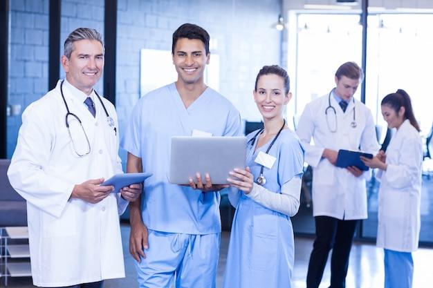 Ritratto di medici che sorridono mentre usando computer portatile e compressa digitale nell'ospedale Foto Premium