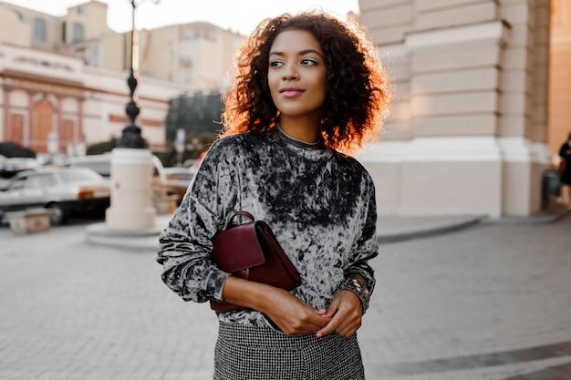 Ritratto di moda all'aperto di glamour sensuale giovane elegante signora nera che indossa un vestito alla moda autunno, maglione di velluto grigio e borsa di lusso. Foto Gratuite