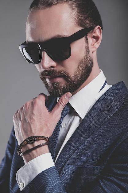 Ritratto di modello di uomo d'affari moda bello vestito in elegante abito blu con occhiali da sole Foto Gratuite