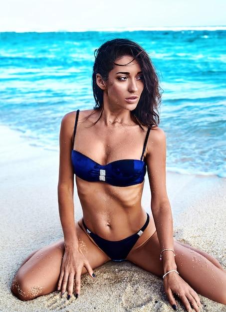 Ritratto di modello indoeuropea bella donna prendisole con capelli lunghi scuri in costume da bagno in posa sulla spiaggia estiva con sabbia bianca su sfondo blu cielo e oceano Foto Gratuite