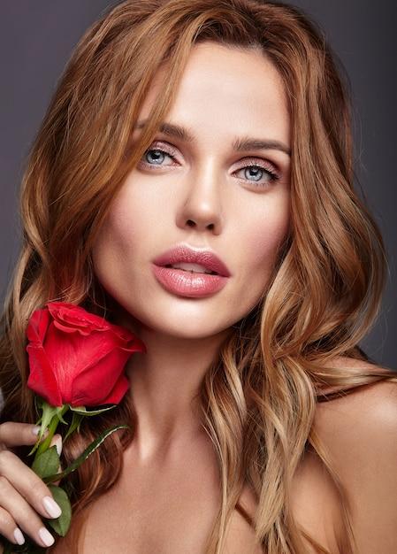 Ritratto di modo di bellezza di giovane modello biondo della donna con trucco naturale e pelle perfetta con la bella posa della rosa Foto Gratuite
