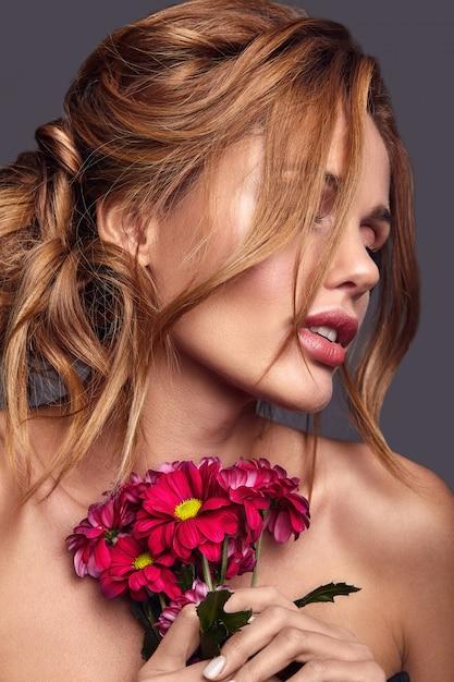 Ritratto di modo di bellezza di giovane modello biondo della donna con trucco naturale e pelle perfetta con la posa luminosa dei fiori Foto Gratuite
