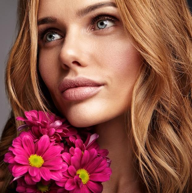 Ritratto di modo di bellezza di giovane modello biondo della donna con trucco naturale e pelle perfetta con la posa luminosa del fiore del crisantemo del? smson Foto Gratuite