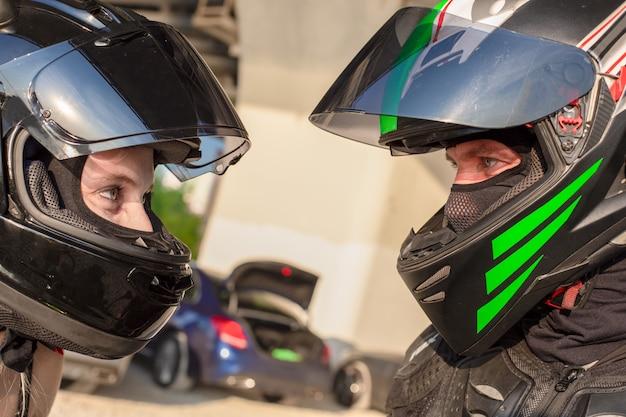 Ritratto di motociclisti uomo e donna in caschi si guardano. concetto di amore moto. cavalieri estremi Foto Premium