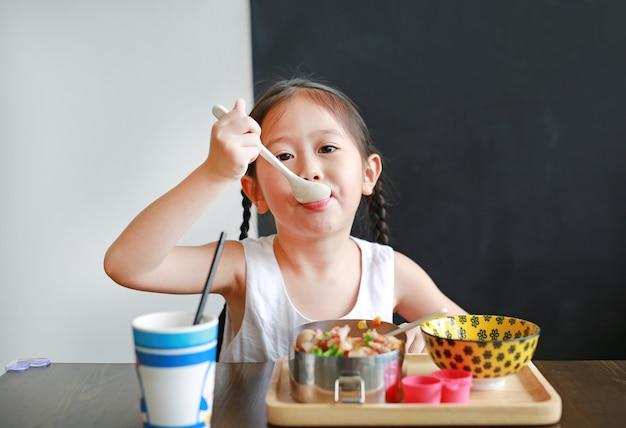 Ritratto di piccola ragazza asiatica del bambino facendo colazione al mattino. Foto Premium