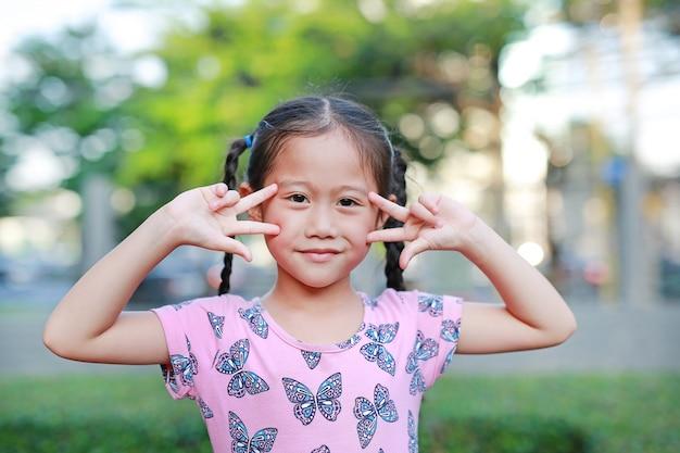 Ritratto di piccola ragazza asiatica felice del bambino con le orecchie di gatto che tengono le dita sul suo fronte. Foto Premium