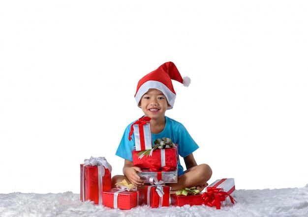 Ritratto di piccolo ragazzo asiatico felice con molti contenitori di regalo isolati su bianco Foto Premium