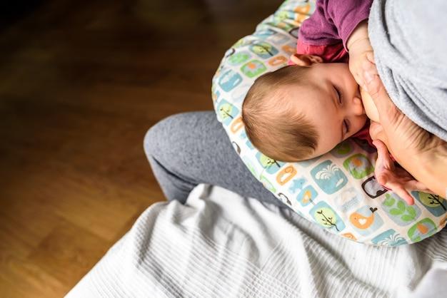 Ritratto di profilo di una giovane donna che allatta al seno un bambino utilizzando un cuscino speciale per l'allattamento al seno per i neonati. Foto Premium