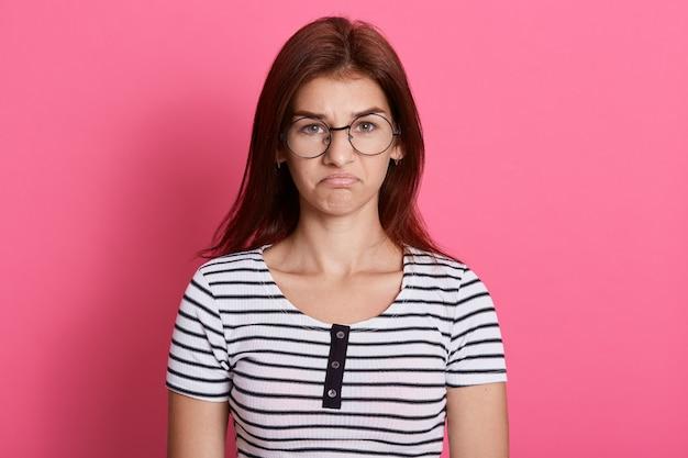 Ritratto di ragazza carina delusa che indossa la maglietta casual a righe con l'espressione facciale sconvolta, in posa isolata sopra la parete rosa. Foto Gratuite