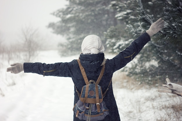 Ritratto di ragazza in forti nevicate, bellezza bambina in maglione e cappello Foto Premium