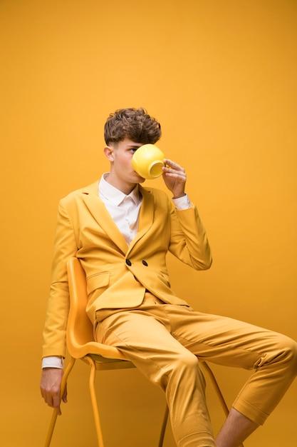Ritratto di ragazzo alla moda che beve da una tazza Foto Gratuite