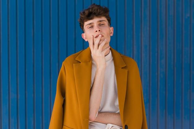 Ritratto di ragazzo alla moda contro il muro blu Foto Gratuite
