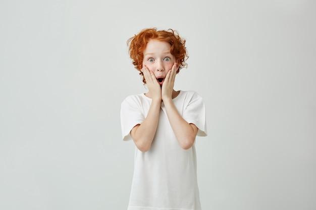 Ritratto di ragazzo carino piccola rossa con le lentiggini in maglietta bianca eccitato Foto Gratuite