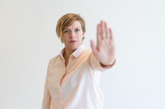 Ritratto di rigoroso metà degli adulti businesswoman facendo fermata gesto Foto Gratuite