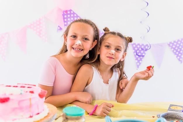 Ritratto di sorelle carina con torta sul loro naso godendo in festa di compleanno Foto Gratuite