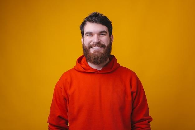Ritratto di sorridente uomo barbuto hipster in camicetta rossa guardando la telecamera Foto Premium