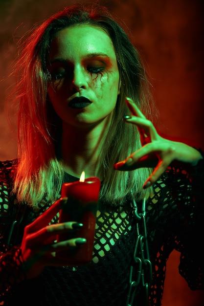 Ritratto di strega con il trucco di halloween con una candela Foto Premium