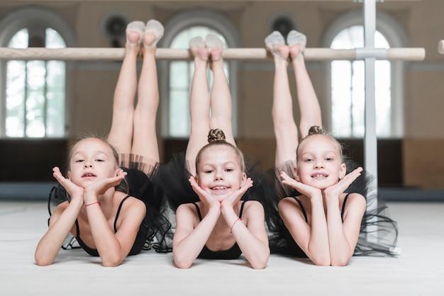 Ritratto di tre ballerine in piedi davanti alla sbarra Foto Gratuite