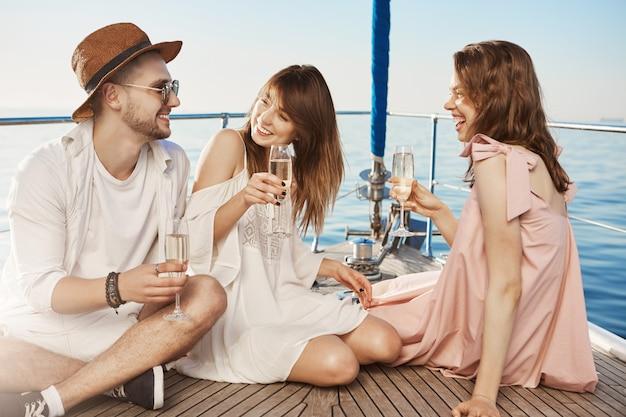 Ritratto di tre persone sedute sul pavimento dell'yacht mentre bevono champagne e ridendo, godendo una vacanza di lusso. due migliori amici si sono innamorati dello stesso ragazzo e ora flirtano con lui. Foto Gratuite