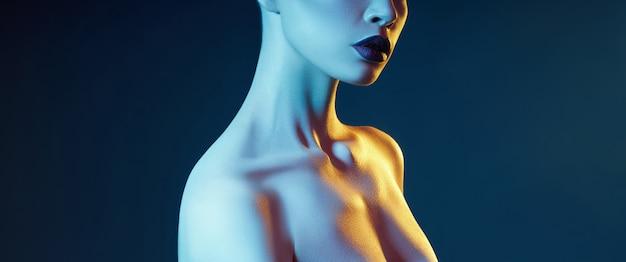 Ritratto di trucco di bellezza contrastante luminoso di una donna nei toni dell'ombra blu e rosso. trucco viso e pelle perfettamente pulito, rossetto scuro su labbra carnose Foto Premium