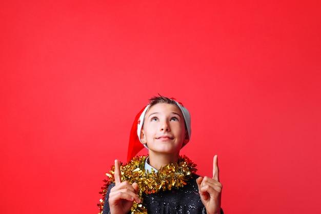 Ritratto di un adolescente in un cappello da babbo natale e con orpelli sul collo rivolto verso l'alto Foto Premium