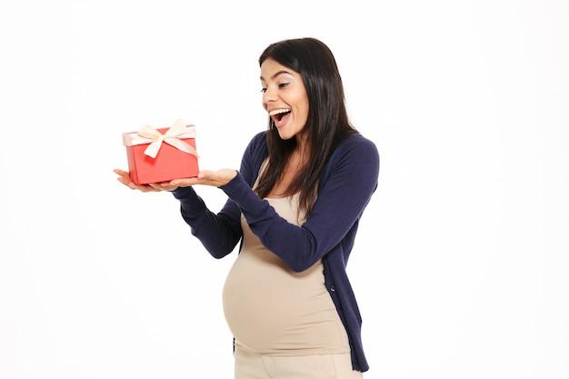 Ritratto di un allegro felice donna incinta con confezione regalo Foto Gratuite