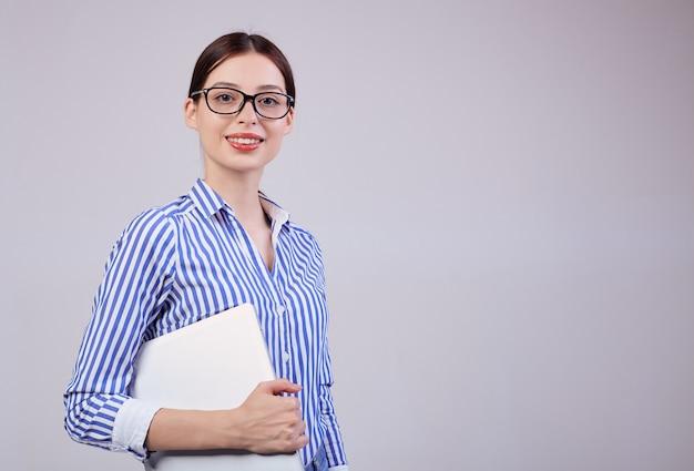 Ritratto di un amministratore femminile in una camicia bianco-blu a strisce con gli occhiali e un computer portatile su grigio. dipendente dell'anno, signora d'affari. Foto Premium