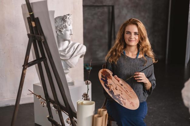 Ritratto di un artista felice con una tavolozza in mano in primo piano Foto Premium