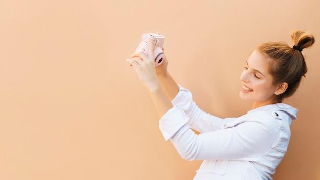 Ritratto di un autoritratto di conversazione sorridente della giovane donna con la macchina fotografica istantanea rosa contro fondo marrone Foto Gratuite