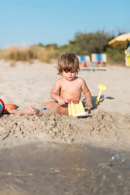 Ritratto di un bambino che fa un castello di sabbia Foto Gratuite