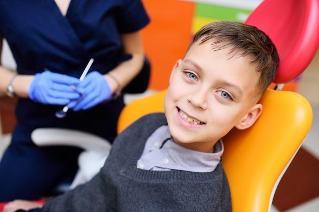Ritratto di un bambino sorridente in una poltrona odontoiatrica. Foto Premium