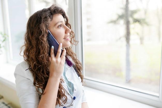 Ritratto di un bel medico parlando al telefono. concetto medico Foto Premium