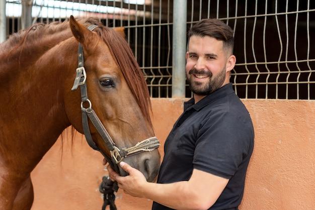 Ritratto di un bell'uomo con il suo cavallo in piedi presso la scuderia Foto Premium