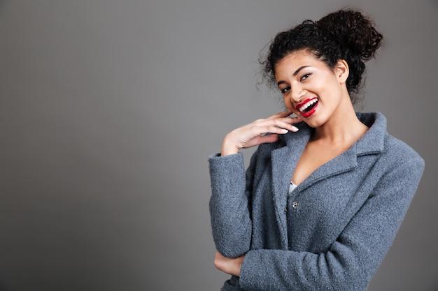 Ritratto di un cappotto da portare sorridente della giovane donna Foto Gratuite