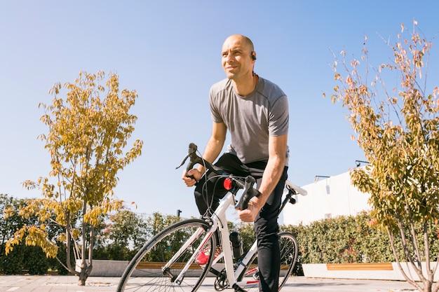 Ritratto di un ciclista maschio seduto sulla bici guardando lontano Foto Gratuite