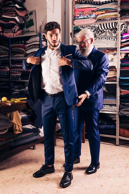 Ritratto di un cliente maschio bello che prova cappotto in negozio Foto Gratuite