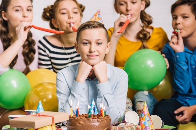 Ritratto di un compleanno ragazzo con i suoi amici che soffia corno di partito Foto Gratuite