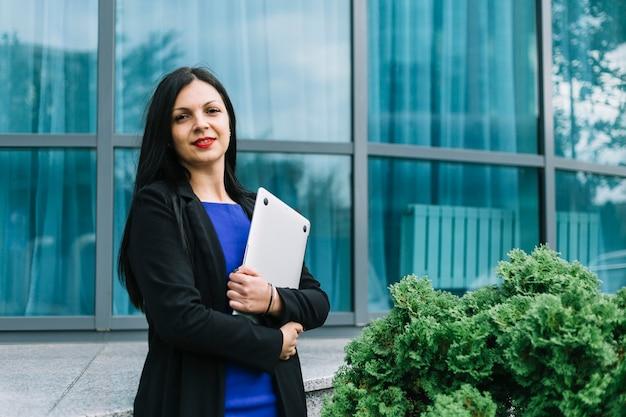 Ritratto di un computer portatile sorridente della tenuta della donna di affari davanti a costruzione di vetro Foto Gratuite