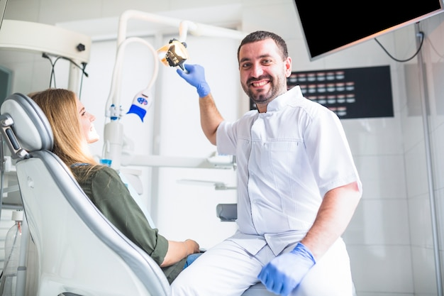 Ritratto di un dentista maschio felice che esamina i denti della femmina Foto Gratuite