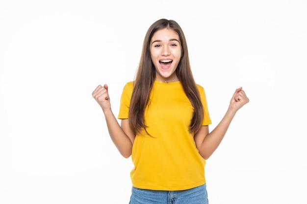 Ritratto di un'eccitata giovane donna che celebra il successo sul muro bianco Foto Gratuite