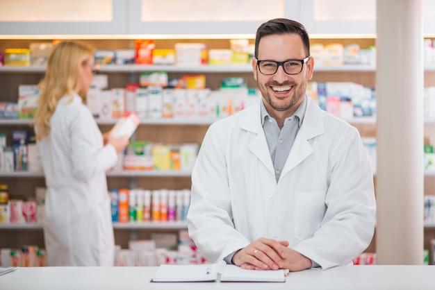 Ritratto di un farmacista bello al bancone di una farmacia, lavoro collega femminile Foto Premium