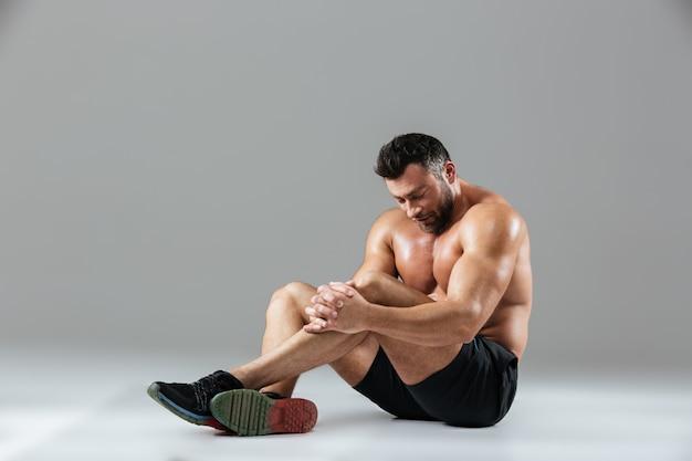 Ritratto di un forte riposo muscolare senza camicia stanco culturista Foto Gratuite