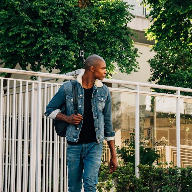 Ritratto di un giovane africano con il suo zaino sulla spalla guardando lontano Foto Gratuite