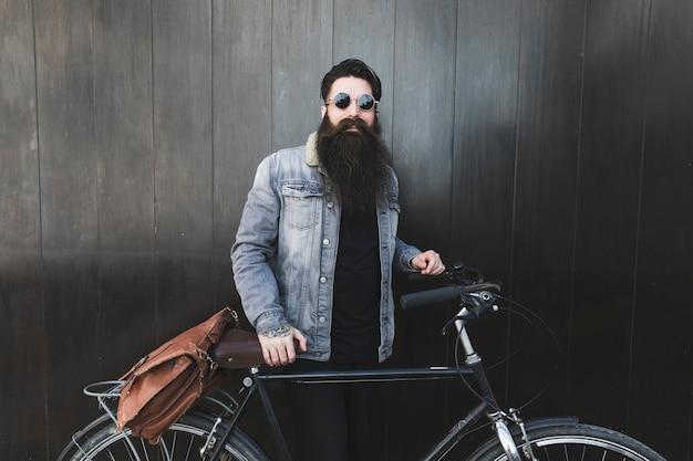 Ritratto di un giovane alla moda indossando occhiali da sole in piedi davanti alla parete in legno nero con la bicicletta Foto Gratuite