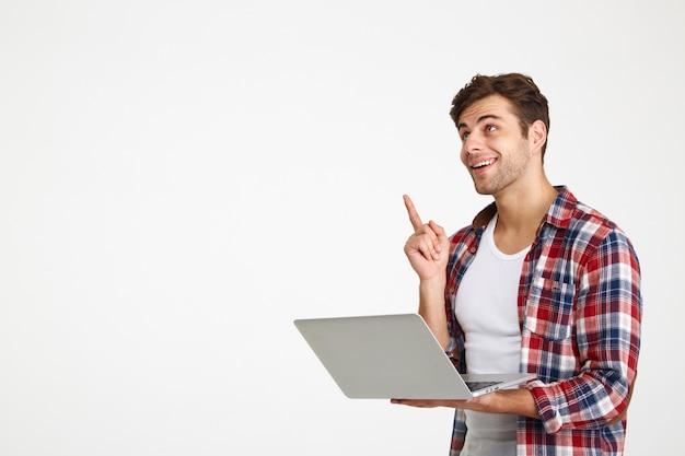 Ritratto di un giovane allegro che tiene computer portatile Foto Gratuite